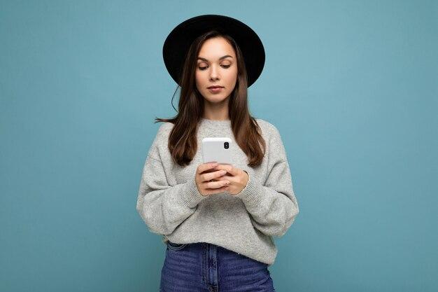 Красивая молодая брюнетка женщина в черной шляпе и сером свитере держит смартфон