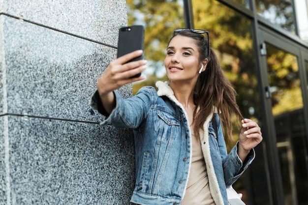 아름 다운 젊은 갈색 머리 여자 재킷을 입고 야외에서 걷고 배낭을 들고, 셀카를 복용