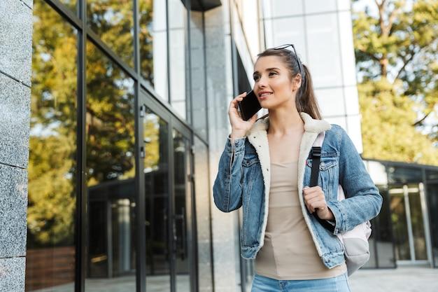 아름 다운 젊은 갈색 머리 여자 재킷을 입고 야외에서 걷고 배낭을 들고, 휴대 전화에 대 한 얘기