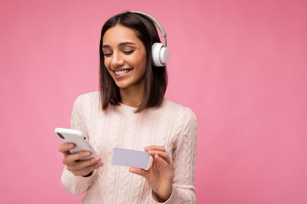 분홍색 배경 위에 절연 분홍색 캐주얼 스웨터를 입고 아름 다운 젊은 갈색 머리 여자