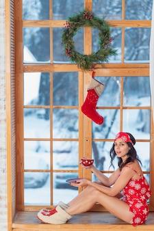 Красивая молодая брюнетка в красной пижаме сидит у окна