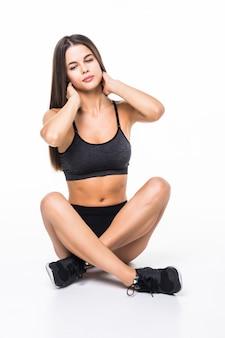 Спортивная одежда красивой молодой женщины брюнет нося сидя на изолированном поле на белизне
