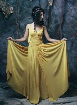 노란색 이브닝 드레스를 입고 아름 다운 젊은 갈색 머리 여자