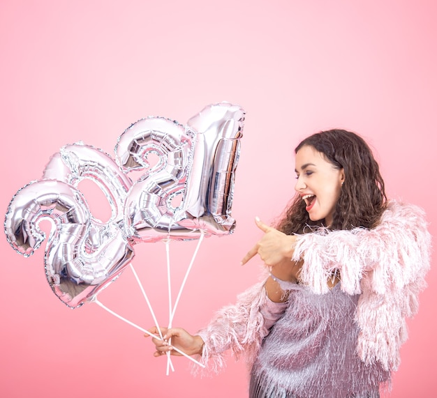 A beautiful young brunette woman with curly hair festively dressed rejoices the new year on a pink wall with warm light with silver balloons for the new year concept