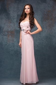 Beautiful young brunette woman with her hair posing in a i long pink dress.