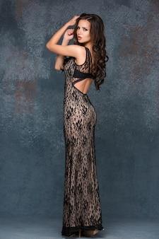 Ai 긴 dack 트레이 서 리 드레스에 포즈를 취하는 그녀의 머리를 가진 아름 다운 젊은 갈색 머리 여자.