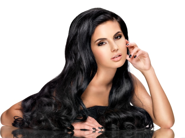 Красивая молодая брюнетка женщина с длинными черными вьющимися волосами позирует в студии