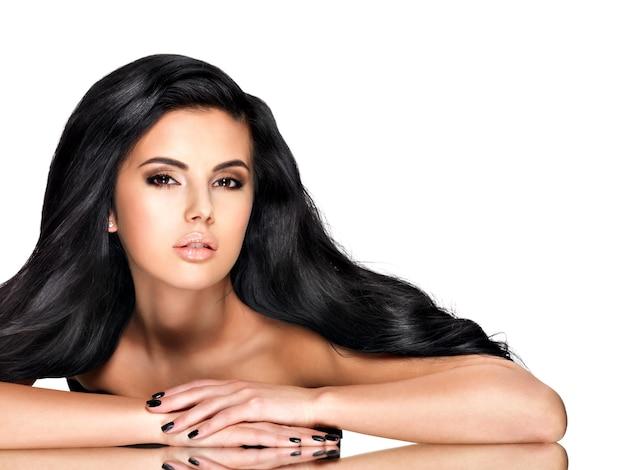Bella giovane donna castana con capelli ricci neri lunghi che posa allo studio