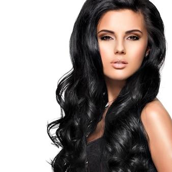 長い黒の巻き毛のポーズで美しい若いブルネットの女性