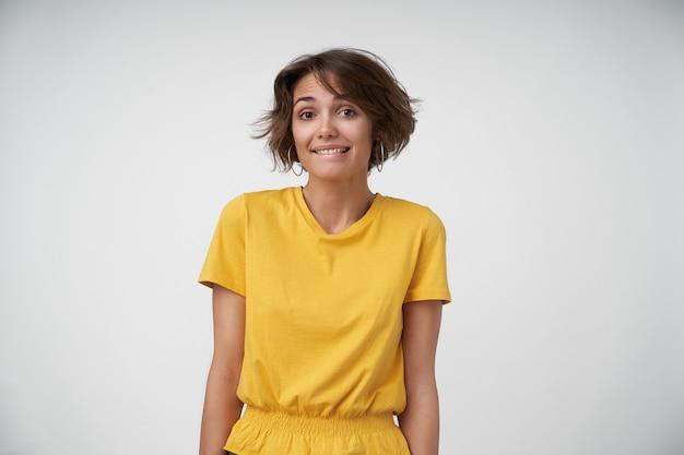짧은 머리가 수줍음을 느끼고 찾고있는 동안 그녀의 입술을 물고있는 아름다운 젊은 갈색 머리 여자, 손으로 포즈를 취하는 동안 노란색 티셔츠를 입고