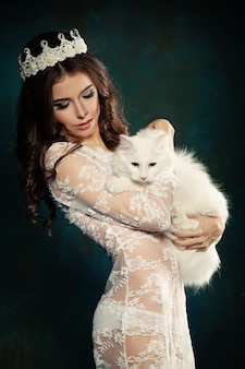 Beautiful young brunette woman with white cat