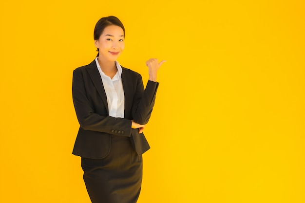 Beautiful young business asian woman with happy smile pointing to the side