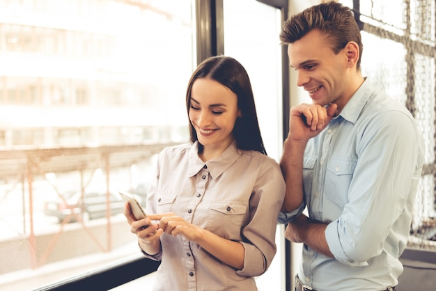 Beautiful young business couple is using a smartphone.