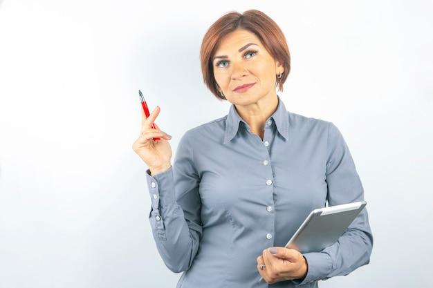 Красивая молодая деловая девушка с красной ручкой и блокнотом в руках