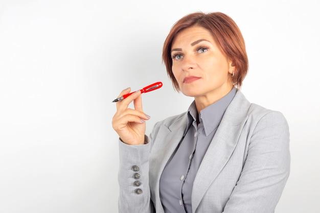 Красивая молодая деловая девушка с красной ручкой в руке на белой поверхности
