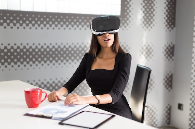 Beautiful young business lady in black strong suite sit at the office table in vr glasses