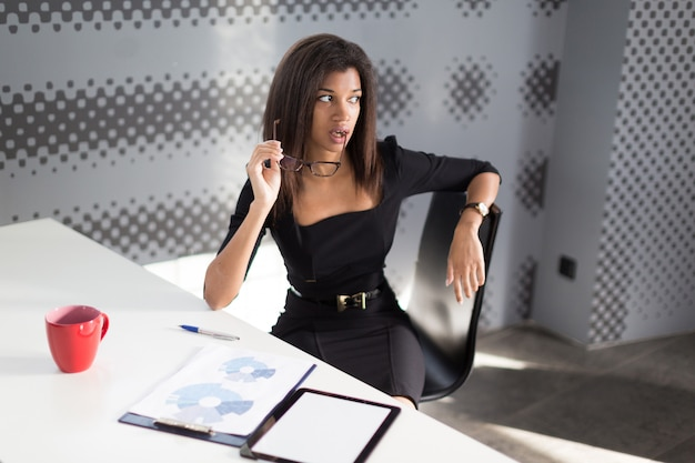 Beautiful young business lady in black strong suite sit at the office table