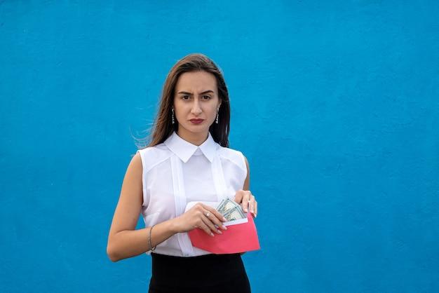 파란색 배경에 달러와 봉투를 들고 아름 다운 젊은 비즈니스 아가씨. 부패의 개념, 봉투 또는 쇼핑의 급여
