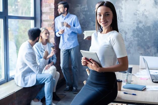 Красивая молодая бизнес-леди смотрит в камеру и улыбается, пока ее коллеги работают в фоновом режиме.