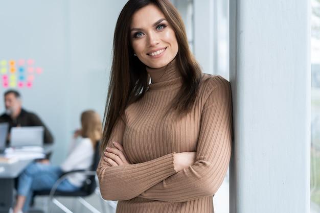 아름 다운 젊은 비즈니스 아가씨 카메라를보고 백그라운드에서 작업하는 그녀의 동료 동안 웃 고.