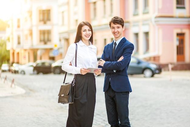 Красивая молодая деловая женщина и красивый бизнесмен в официальных костюмах используют цифровой планшет