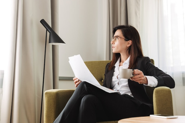 Beautiful young business woman in formal wear clothes indoors at home drinking coffee work with documents.