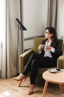 Beautiful young business woman in formal wear clothes indoors at home drinking coffee.