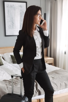 Beautiful young business woman in formal wear clothes indoors at home with suitcase talking by mobile phone.