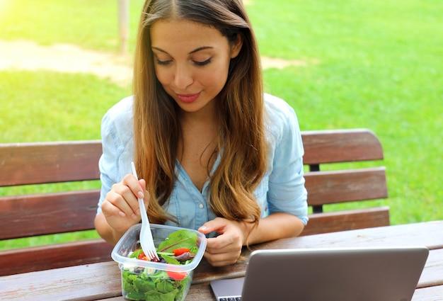 Красивая молодая бизнес-леди обедает, сидя в городском парке.