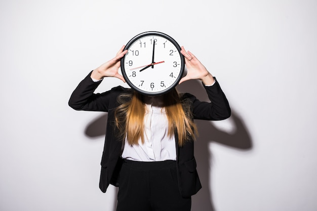 Beautiful young business woman holding clock in front of face on white