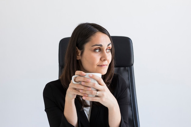 Beautiful young business woman holding a cup of coffee.