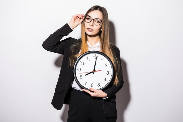 Beautiful young business woman holding in hands clock on white
