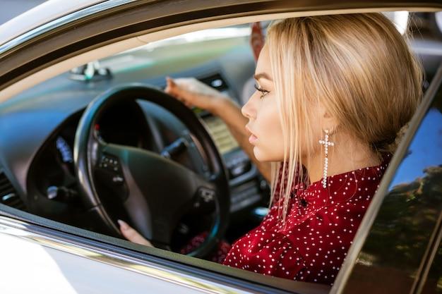 車の運転に座っている赤いドレスの美しい若いビジネス女性