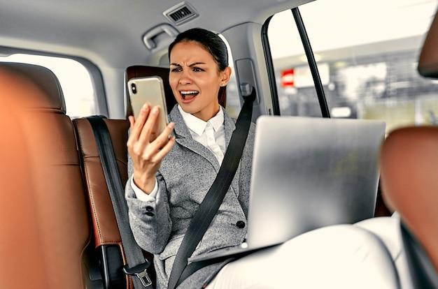 차에서 아름 다운 젊은 비즈니스 우먼 전화에 놀란 모습과 노트북에서 작동합니다.