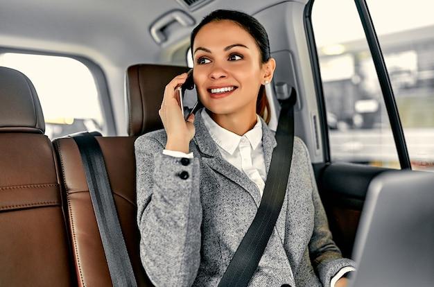 전화 통화하는 차에서 아름 다운 젊은 비즈니스 여자와 노트북에서 작동합니다.