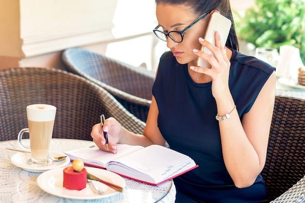 Красивая молодая деловая женщина звонит с помощью смартфона во время записи дневника в кафе на открытом воздухе.