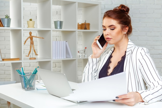 Beautiful young business woman is using a smartphone, working in office
