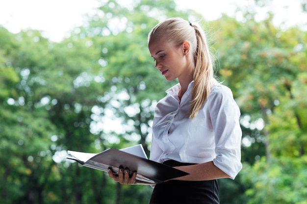Beautiful young business woman looking through documents while standing outdoos