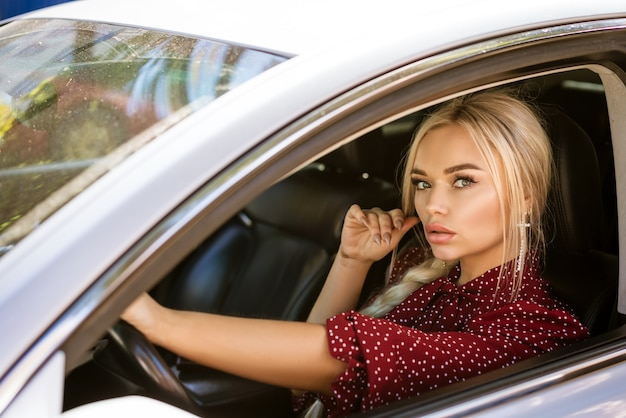 Beautiful young business woman in a red dress sitting in a car
