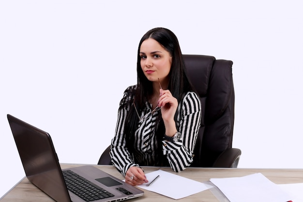 Beautiful young business woman sitting on chair working with laptop on white wall