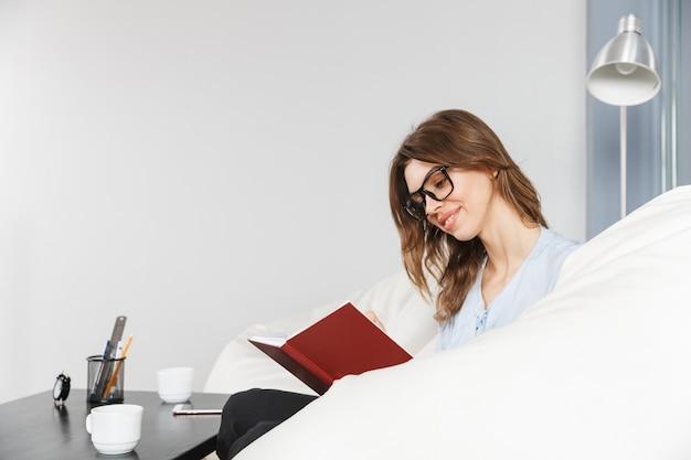 Красивая молодая деловая женщина, сидя на диване в офисе, читая книгу