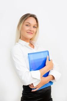 Красивая молодая бизнес-леди усмехаясь смотря камеру с голубой папкой в руках, с белой стеной.