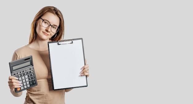 안경을 쓰고 아름 다운 젊은 비즈니스 우먼 회색 공간에 고립 된 빈 공간을 모의 계산기와 클립 보드를 보유