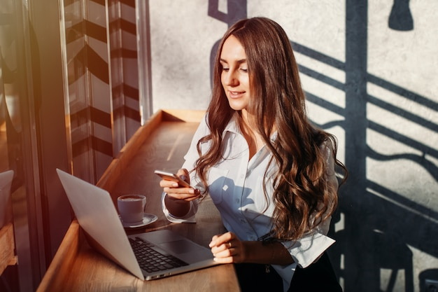 Beautiful young business woman in white blouse using laptop and smartphone, drinks coffee at a table in a cafe