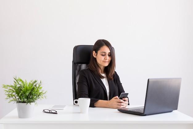 彼女のラップトップと携帯電話を使用して、オフィスで働く美しい若いビジネス女性