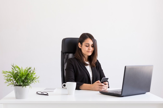 Beautiful young business woman working in the office, using her laptop and mobile phone