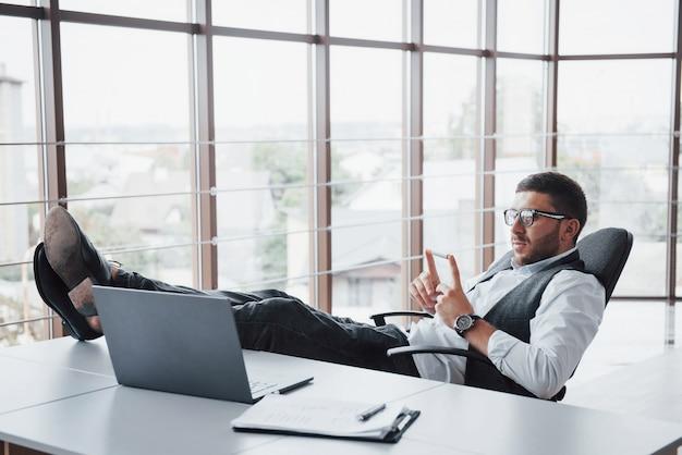 테이블에 자신의 다리를 잡고 안경을 가진 아름 다운 젊은 사업가 사무실에서 노트북을 찾고