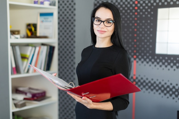 Beautiful young businesswoman in black dress and glasses hold paper folder