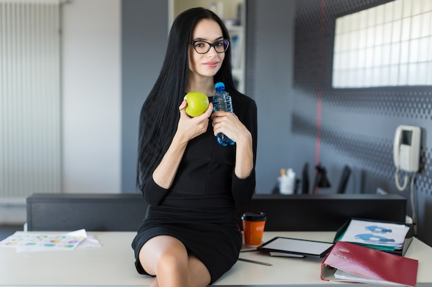 Beautiful young businesswoman in black dress and glasses sit on table in the office and hold green apple and bottle