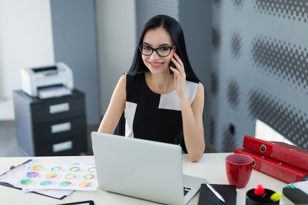 Beautiful young businesswoman in black dress and glasses sit at the table, work and talk a phone